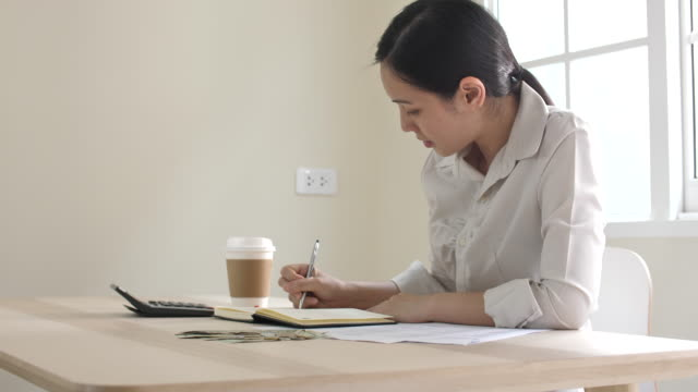 woman working on financial reports at home - paying tax stock videos & royalty-free footage