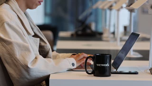woman working on her laptop, drinking from cup with wework co-working space logo in london, england, uk, on monday, august 2, 2021. - working stock videos & royalty-free footage