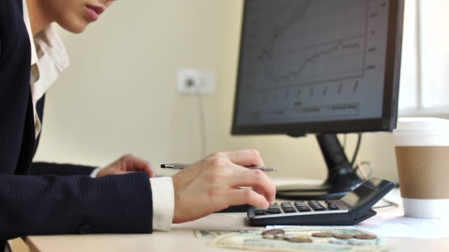 Woman working on Home financial reports Calculator For Taxes And Budget At Home