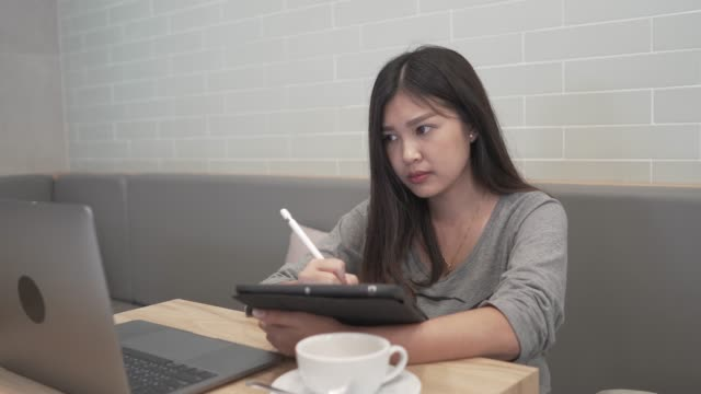 woman working on laptop and digital tablet using stylus pen at cafe - pen stock videos & royalty-free footage