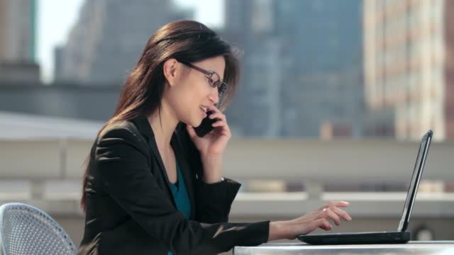 vídeos de stock, filmes e b-roll de woman working on laptop and talking on phone - café de calçada