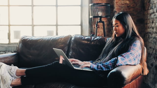 woman working on laptop - プレイドシャツ点の映像素材/bロール
