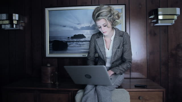 ms woman working on laptop while sitting on dresser in tacky hotel room / palmdale, ca, united states - artistic product stock videos & royalty-free footage