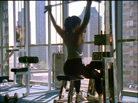 REAR VIEW woman working on lat pull-down weight machine by window in gym / NYC