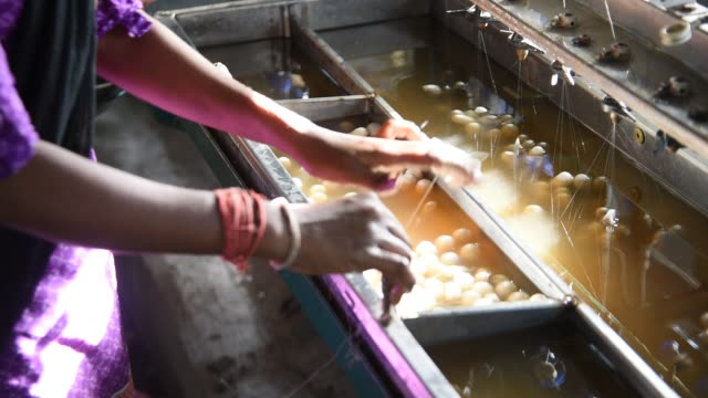 woman working on silk making machine from cocoon of silkworm - silk stock videos & royalty-free footage