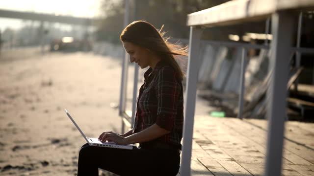 vídeos y material grabado en eventos de stock de mujer que trabaja en la playa por el río - camisa a cuadros