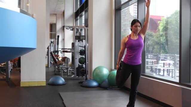 woman working out in the gym, doing yoga. - auf einem bein stock-videos und b-roll-filmmaterial