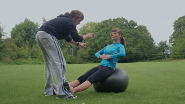 ms woman working out on exercise ball with personal trainer in park, london, england - fitness ball stock videos & royalty-free footage