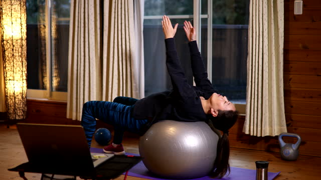woman working out with a yoga ball online at home - fitness ball stock videos & royalty-free footage