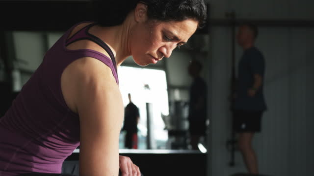 woman working out with dumbbells at the gym - bizeps stock-videos und b-roll-filmmaterial