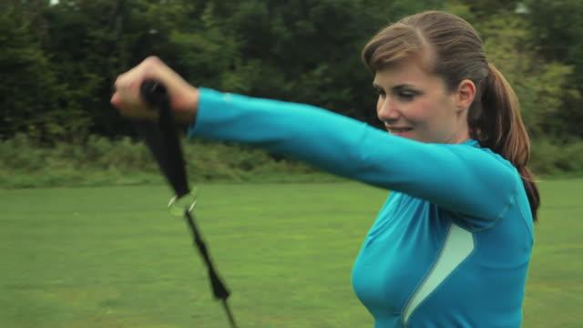 vidéos et rushes de ms pan woman working out with resistance bands in park, london, england - une seule femme d'âge moyen