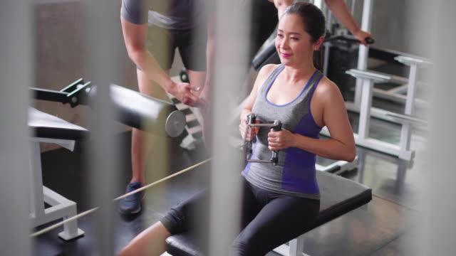 vídeos y material grabado en eventos de stock de mujer haciendo ejercicio con entrenador en gimnasio - equilibrio vida trabajo