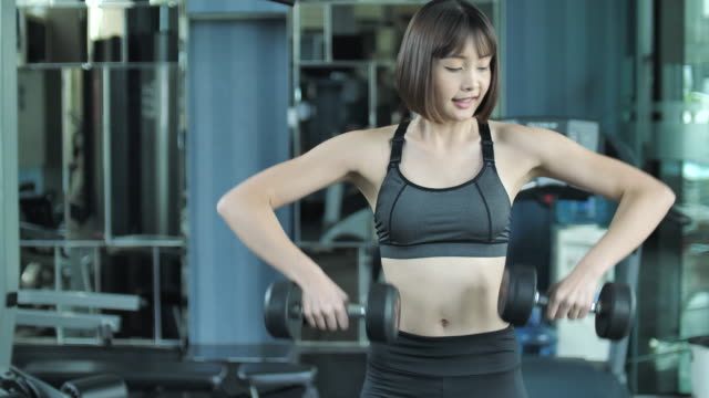 Woman Working Out With Weights In Gym