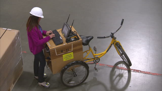 ms aerial woman working with computer mounted on back of tricycle in warehouse / lebec, ca, united states      - tricycle stock videos & royalty-free footage