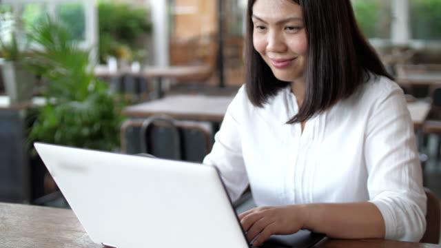 vídeos y material grabado en eventos de stock de mujer que trabaja con computadora portátil en el café - espacio de trabajo virtual compartido
