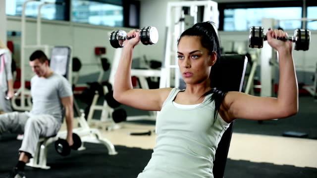 frau training mit gewichten im fitnessstudio - menschlicher muskel stock-videos und b-roll-filmmaterial