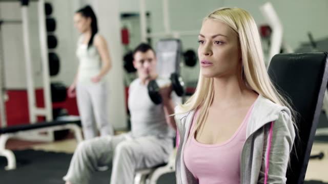 vidéos et rushes de femme travaillant avec des haltères dans la salle de sport - poids pour la musculation
