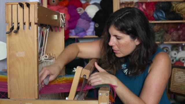 vídeos de stock e filmes b-roll de woman working working on a loom - só mulheres de idade mediana