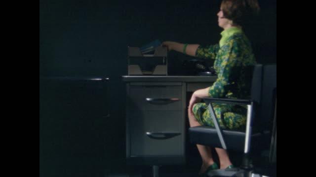 woman works alone at desk in dark room - secretary stock videos & royalty-free footage