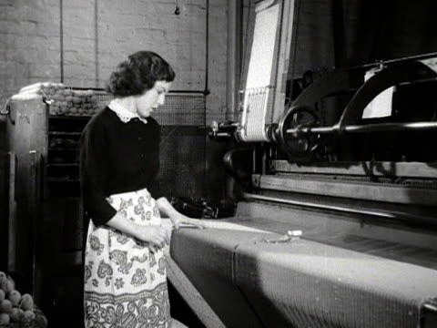 A woman works at a chenille loom making a carpet which will placed outside Westminster Abbey for the Coronation of Elizabeth the second 1953