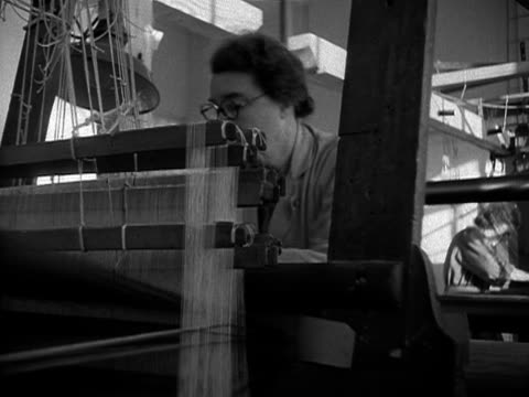 woman works at a large loom creating the velvet fabric that will be used for the coronation robe for elizabeth the second. 1953. - ベルベット点の映像素材/bロール