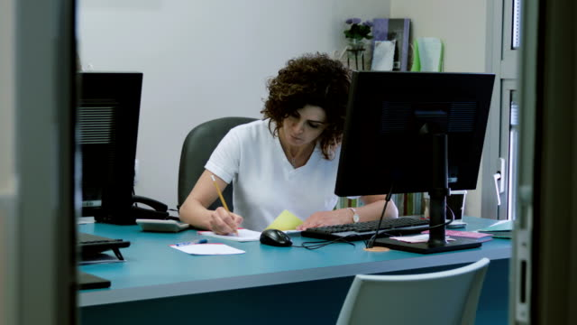 Woman works at the computer making notes and calculations