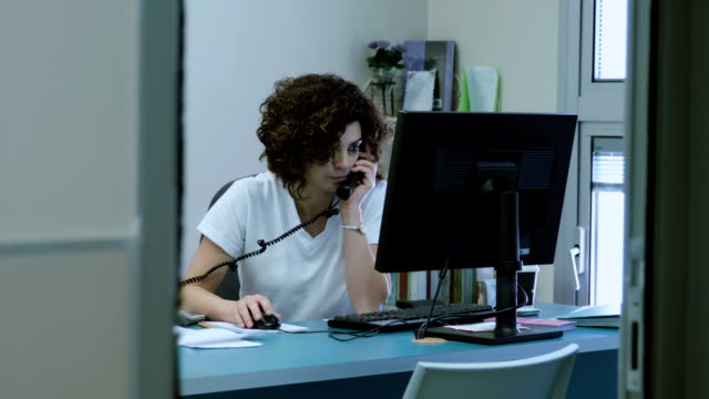 Woman works at the computer talking on the phone