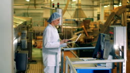 A woman works with a laptop at a food production factory.