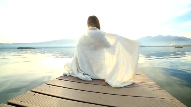 woman wrapped in blanket on wooden jetty - blanket stock videos and b-roll footage
