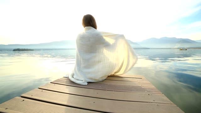 Frau in eine Decke eingewickelt auf hölzernen Anlegesteg