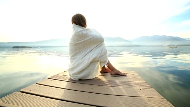 woman wrapped in blanket on wooden jetty - jetty stock videos & royalty-free footage
