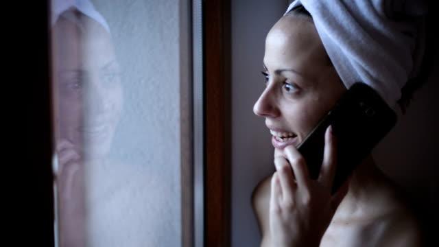 女性は、タオルに包まれた携帯電話を使用して - タオルにくるまる点の映像素材/bロール