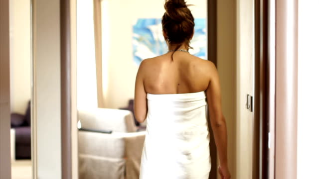 Woman wrapped in towel walking from bathroom to bedroom