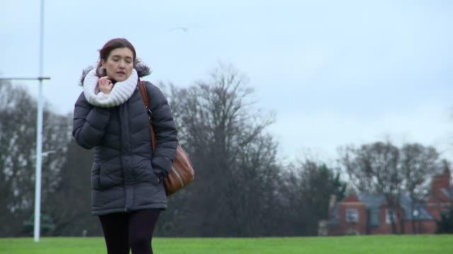vídeos de stock, filmes e b-roll de a woman wrapped up for winter walks across a park - neckwear