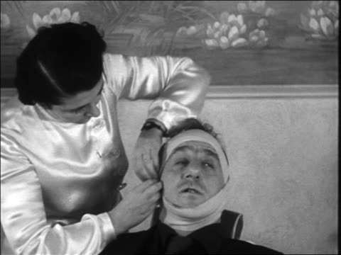 B/W 1938 woman wrapping bandages around head of Jimmy Durante in chair in beauty parlor / newsreel