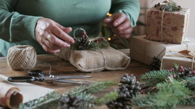 vídeos y material grabado en eventos de stock de mujer envolviendo regalos de navidad. - piña de piñones