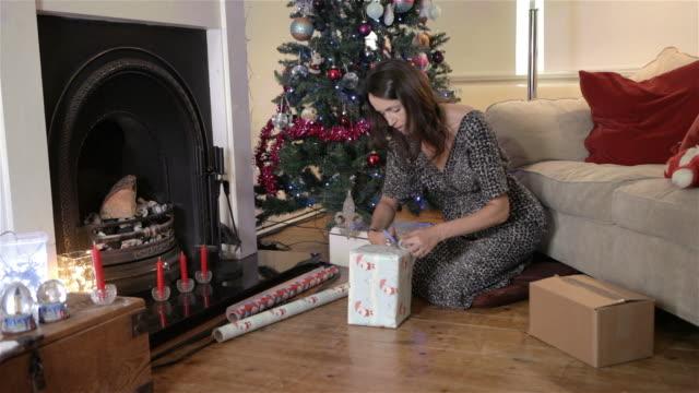 frau, die weihnachtsgeschenke verpackt - one mature woman only stock-videos und b-roll-filmmaterial
