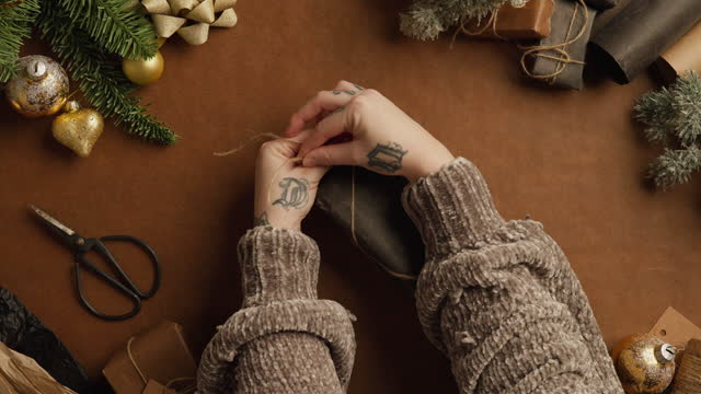 vídeos de stock e filmes b-roll de woman wrapping gifts for christmas - top down view - cordel