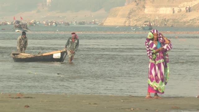 ws, woman wrapping in traditional scarf on ganges river bank, two men pulling boat in background, allahabad, uttar pradesh, india - 引く点の映像素材/bロール
