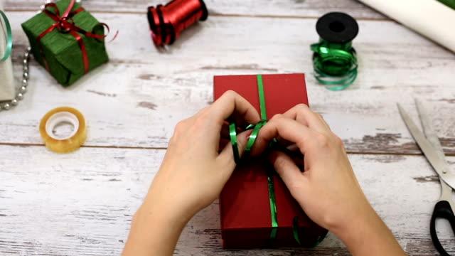 Donna moderna presenta la confezione regali di Natale a casa