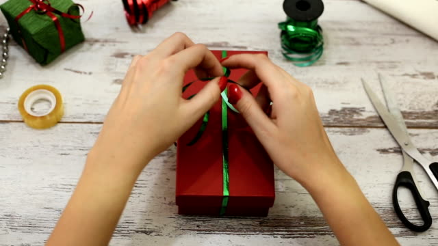Woman wrapping modern Christmas gifts presents at home