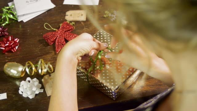 Woman Wraps a Green Ribbon Around a Christmas Gift
