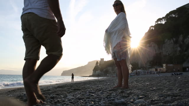 Woman wraps blanket around herself and man, beach