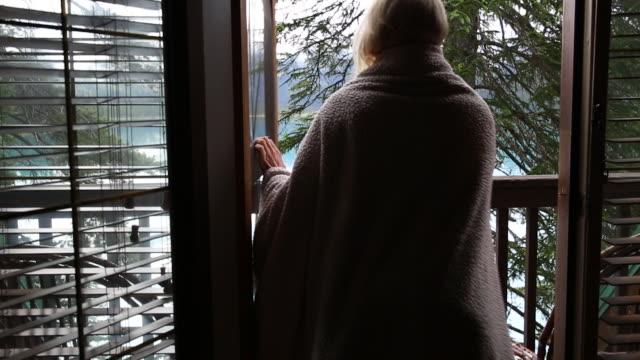 woman wraps herself in blanket, on deck overlooking lake - eingewickelt stock-videos und b-roll-filmmaterial