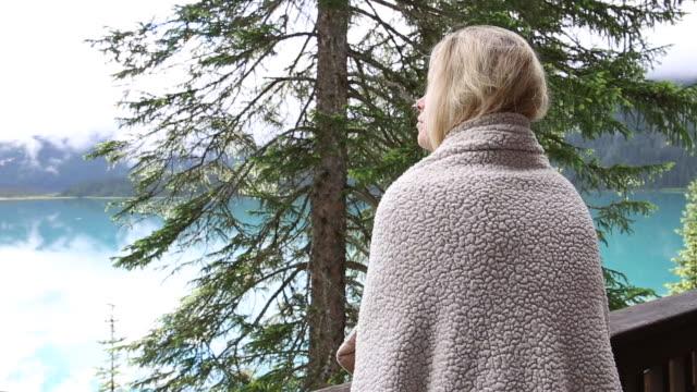 Woman wraps herself in blanket, on deck overlooking lake