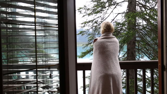 Woman wraps herself in blanket, on deck overlooking lake