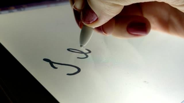 frau schreibt, ich liebe mein haustier auf der elektronischen tafel mit einem touch-pen - menschliche gliedmaßen stock-videos und b-roll-filmmaterial