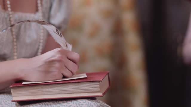 vidéos et rushes de la femme écrit avec la plume dans le costume d'époque. - littérature