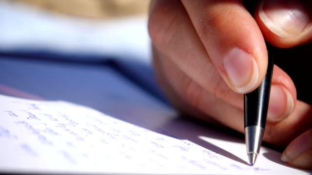 Woman writing a postcard in the sun.