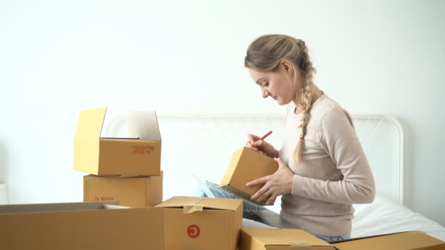 vídeos de stock e filmes b-roll de woman writing address on parcel, e-commerce - agenda de telefones